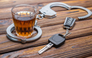 Concept drunkenness driving. Handcuffs, a glass of alcohol, car keys.